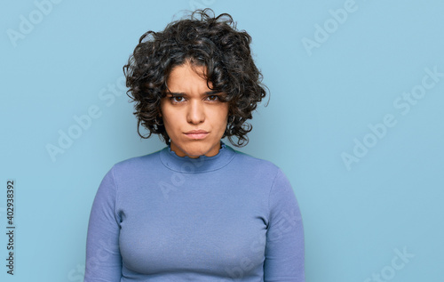 Obraz na plátně Young hispanic woman with curly hair wearing casual clothes skeptic and nervous, frowning upset because of problem