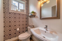 Sink Toilet And Mirror Inside Residential Bathroom With Decorative Accent Wall