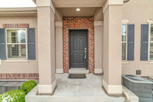 House Entrance With Portico Leading To Front Door Against Red Brick Wall