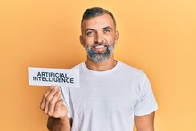 Middle Age Handsome Man Holding Artificial Intelligence Word On Paper Looking Positive And Happy Standing And Smiling With A Confident Smile Showing Teeth