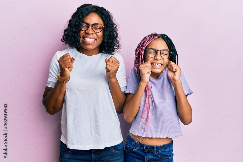 Fototapeta Beautiful african american mother and daughter wearing casual clothes and glasses excited for success with arms raised and eyes closed celebrating victory smiling. winner concept.