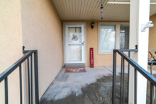 Porch And White Front Door With Glass Storm Door Viewed From The Outdoor Steps