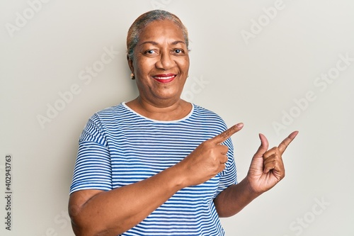 Senior african american woman wearing casual clothes smiling and looking at the camera pointing with two hands and fingers to the side. - fototapety na wymiar