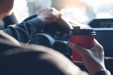 Man Holding Cup Of Coffee While Driving A Car In The Morning