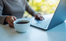 Closeup Image Of A Woman Working And Touching On Laptop Computer Touchpad While Drinking Coffee