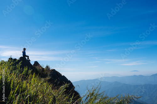 Obraz A female traveler hiking and sitting on mountain peak, looking at a beautiful view - fototapety do salonu
