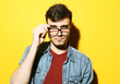 Leinwandbild Motiv Portrait of a smart young man wearing eyeglasses standing against yellow background