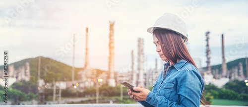 Obraz Woman engineer entrepreneur construction industry worker. Female engineer working refinery oil plant manufacturing. Young civil engineering construction wear hard hat safety helmet construction site. - fototapety do salonu