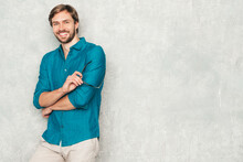 Portrait Of Handsome Smiling Hipster Lumbersexual Businessman Model Wearing Casual Jeans Shirt Clothes. Fashion Stylish Man Posing Against Gray Wall In Studio In Eyewear