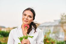 Close Up Portrait Of Beautiful Mature Woman Enjoying Nice Day In Garden, Holding Pink Zinnia Flower