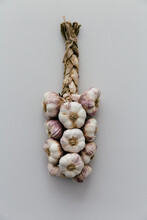 Rustic Plaited String Of Garlic On A Light Grey Clean And Neutral Table.