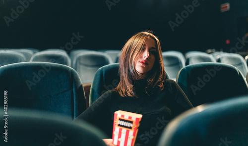 Obraz na plátně Bella ragazza seduta al cinema con pop corn si guarda un film