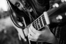 Close-up Fingers On The Strings, Girl Playing Acoustic Guitar. Black And White Photo.