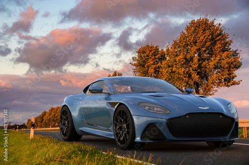 Aston Martin DBS superleggera on a scenic road at sunset