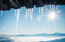 Spectacular Icicles Shine In Sun Against Blue Sky. Splendid View With Ice Icicles Hanging From Roof.