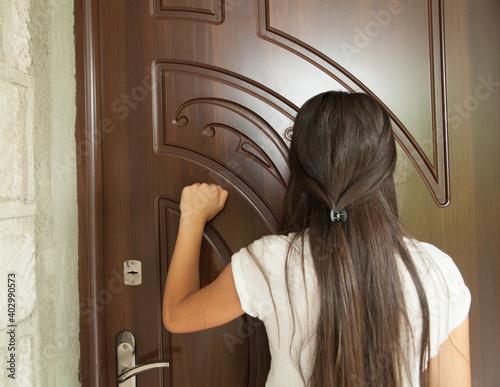 Foto Woman knocks on the house door.