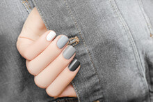 Female Hand With Silver Nail Design. Black Nail Polish Manicure. Woman Hand On Gray Ragged Denim Fabric Background
