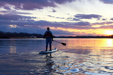 Boy Rowing On Stand Up Paddle Boarding (SUP) Paddling Along The Calm Autumn Danube River Against Background Of A Colorful Sunset. The Concept Of Children's Sports And Tourism.