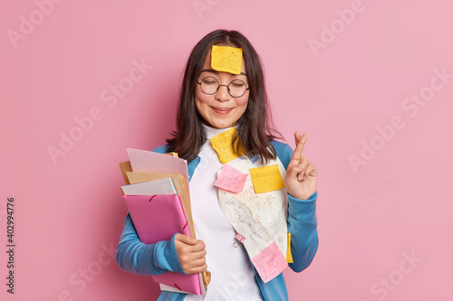 Positive schoolgirl crosses fingers believes in good luck on exam wears round spectacles stuck with papers and sticky notes written information to remember makes crib. Student uses cheat sheets.
