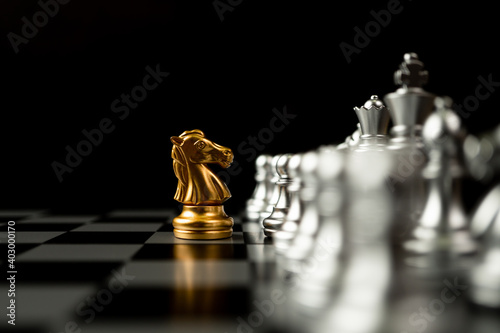 Leinwand Poster Golden horse chess standing in front of other chess, Concept of a leader must ha