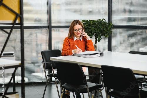 Fototapeta Portrait of happy lady typing in mobile while locating at desk in office obraz na płótnie