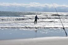 Solitary Fisherman Surf Fishing In Ocean Beach