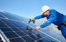Male Engineer In Blue Suit And Protective Helmet Installing Stand-alone Solar Photovoltaic Panel System Using Screwdriver. Electrician Mounting Blue Solar Module On Roof Of Modern House.