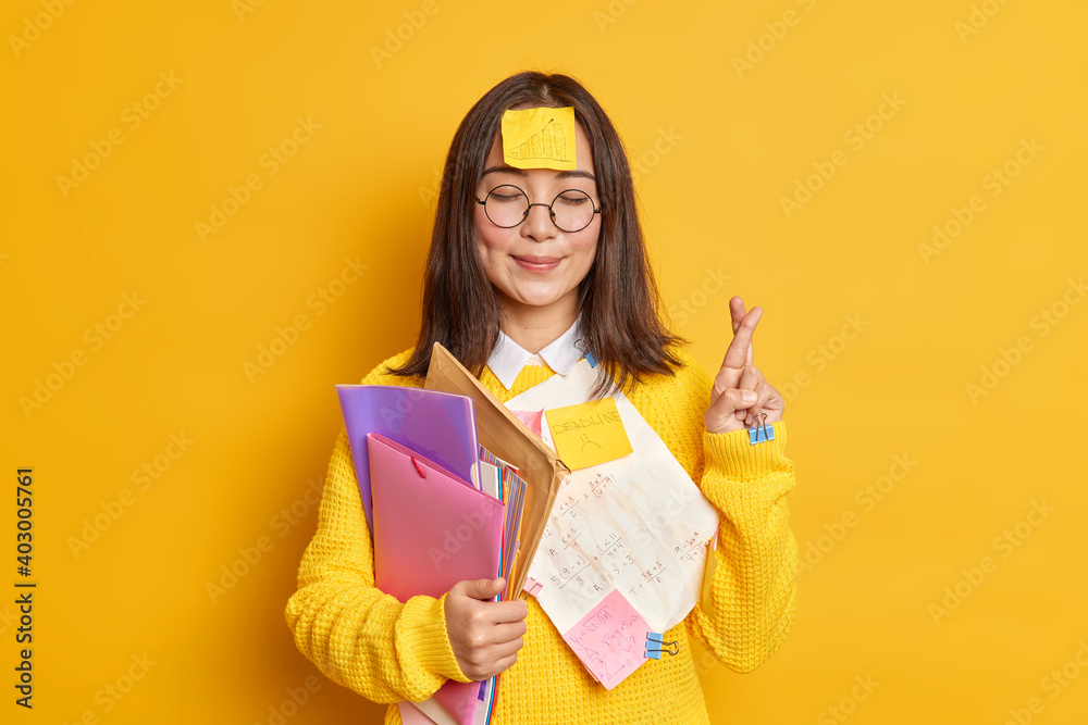 Fototapeta Pleased Asain female student believes in good luck at exam stands with eyes closed and fingers crossed believes dreams come true stuck with papers holds folders isolated over yellow background