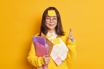 Fototapeta Boks Pleased Asain female student believes in good luck at exam stands with eyes closed and fingers crossed believes dreams come true stuck with papers holds folders isolated over yellow background