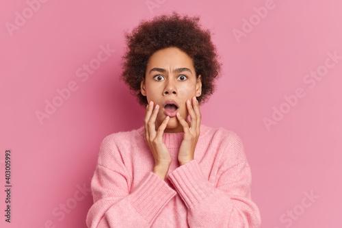 Billede på lærred Portrait of shocked curly haired millennial girl keeps mouth opened hands on che