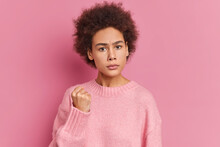 Young Afro American Woman Shows Fist Has Annoyed Face Expression Going To Revenge Or Threaten Someone Makes Serious Look Wears Casual Sweater Isolated Over Pink Background. I Will Show You Who Is Boss