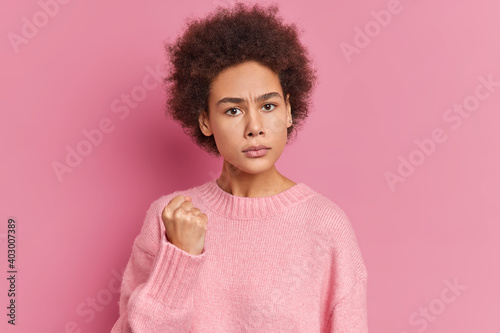 Fotografia, Obraz Young Afro American woman shows fist has annoyed face expression going to revenge or threaten someone makes serious look wears casual sweater isolated over pink background