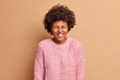 Leinwandbild Motiv Amused carefree African American woman closes eyes and smiles broadly expresses pure emotions speaks to funny friend wears warm knitted sweater poses against beige background laughs out loudly