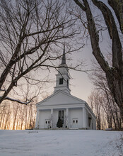 Classic New England White Church On Village Green On A Winter Evening