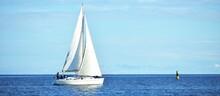 White Sloop Rigged Yacht Sailing Near The Lighthouse, Close-up. Riga Bay, Baltic Sea. Clear Blue Sky. Transportation, Nautical Vessel, Cruise, Sport, Regatta, Recreation, Leisure Activity