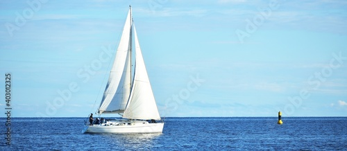 Fototapeta White sloop rigged yacht sailing near the lighthouse, close-up