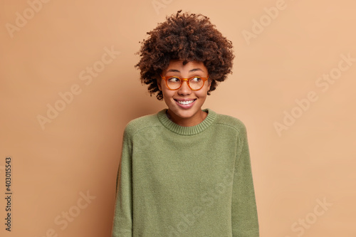 Portrait of pretty positive ethnic woman looks aside with toothy smile sees something nice wears casual long sleeved jumper and spectacles poses in studio against brown background. Good emotions