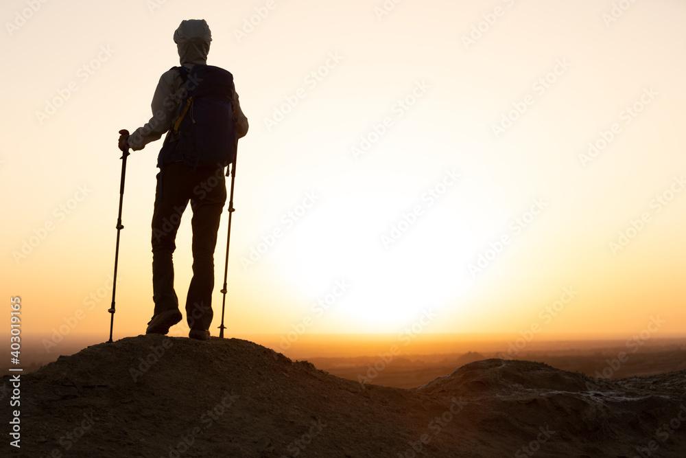 Fototapeta Successful woman hiker enjoy the view on sand desert in the sunset