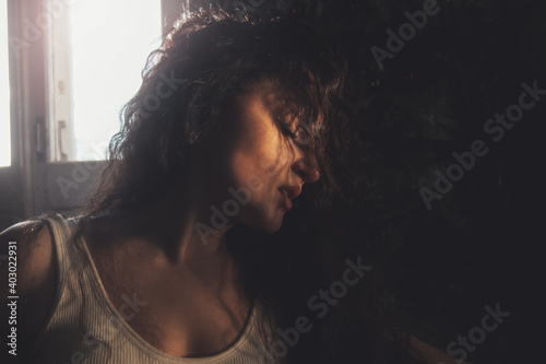 Fototapeta portrait of a curly girl in dark colors