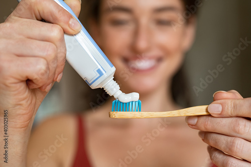 Obraz Woman applying toothpaste on bamboo toothbrush - fototapety do salonu