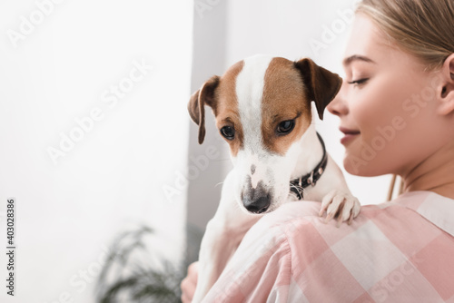 Fototapeta blurred cheerful woman holding in arms jack russell terrier obraz