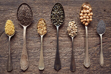 Chia, Millet, Chickpeas, Poppy And Other Seeds And Legumes On Seven Vintage Spoons - Top View