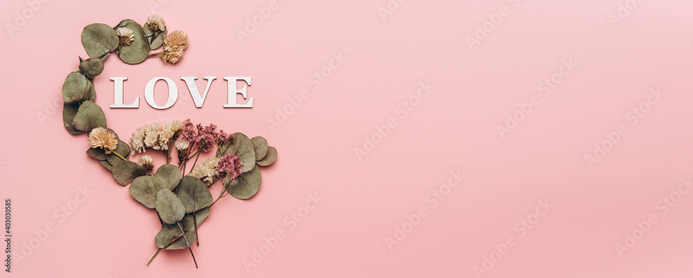 Fototapeta Creative flat lay of word love on soft color  background with natural plants
