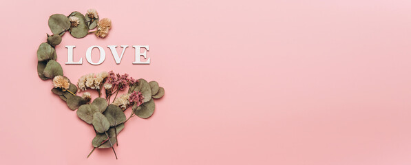 Creative flat lay of word love on soft color background with natural plants
