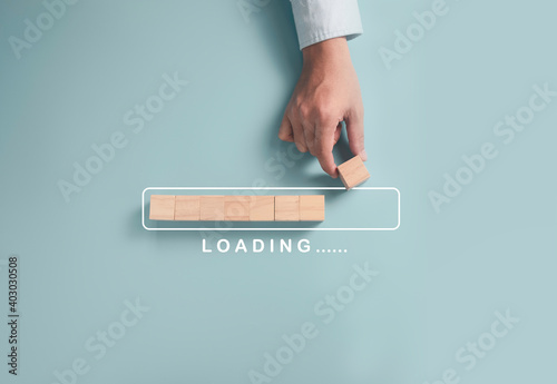 Download Upload data information and business progressive concept, Businessman putting wooden cube block on light blue background.