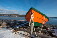 Bright Orange And Green Colourful Wooden Boat On A Beach. There Is A Blue Ocean, Large Trees Covering A Mountain With Snow In The Background, Snow On The Ground And A Blue Sky With Small White Clouds.