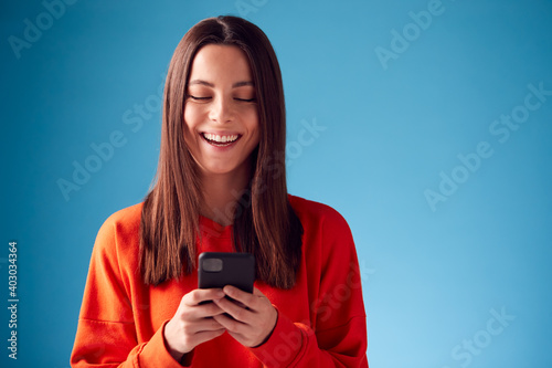 Obraz Studio Portrait Of Smiling Young Woman Looking At Mobile Phone Against Blue Background - fototapety do salonu