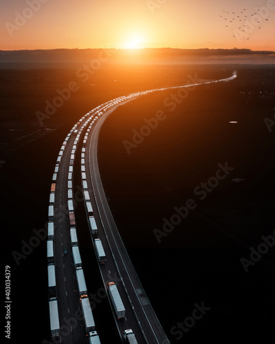 Obraz Aerial drone shot of a big traffic jam of Trucks that wait in line for border crossing control from the United Kingdom to France on the M20 before Dover - fototapety do salonu