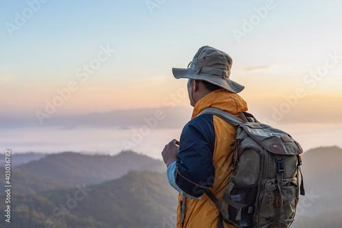 Obraz Hipster male hiker with backpack enjoying sunset on peak of foggy mountain. Tourist traveler on background view mockup. - fototapety do salonu