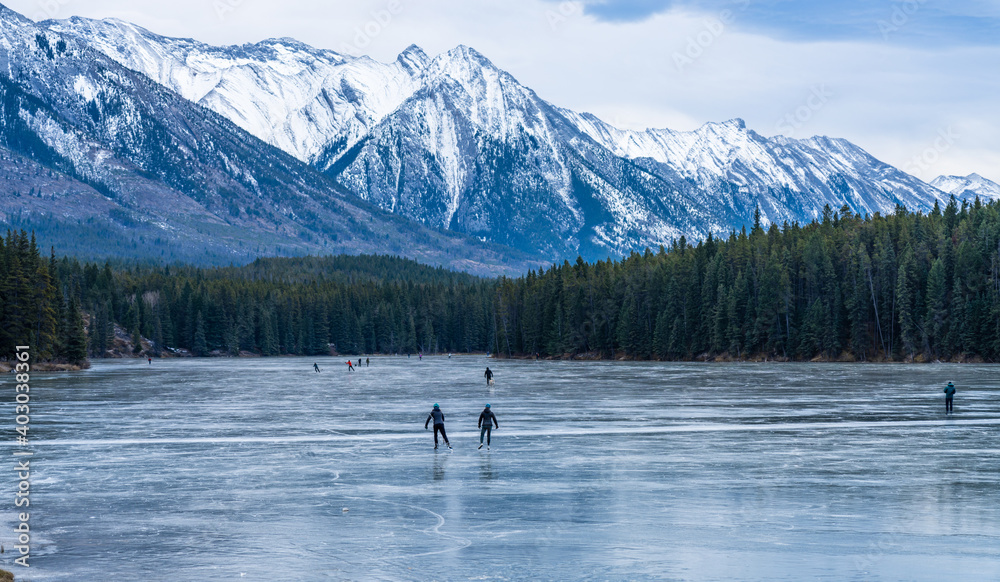 Fototapeta Tourists doing ice-skating in Johnson Lake frozen water surface in winter time. Snow-covered mountain in the background. Banff National Park, Canadian Rockies, Alberta, Canada.
